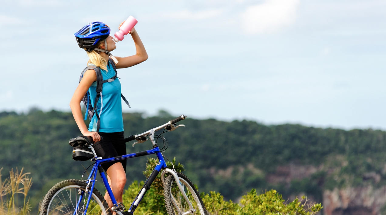 Attractive, healthy woman drinks from her water bottle on mounta