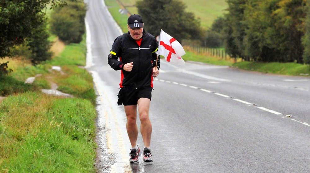 Actor/comedian Eddie Izzard soaking wet as he runs through Wiltshire holding a St Georges Flag. Izzard will be running more than 1,000 miles around the UK in seven weeks. The star will need to run approximately one marathon per day  to achieve his goal to raise money for Sport Relief Wiltshire, England - 29.07.09 Mandatory Credit: WENN.com